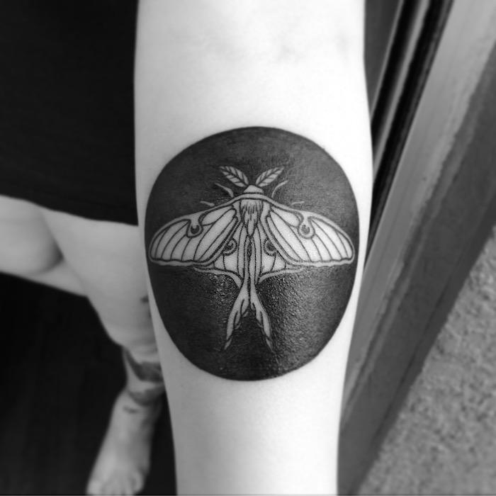 schwarzer Kreis mit einem Insekten in der Mitte Tattoo am Arm - Tattoo Arten