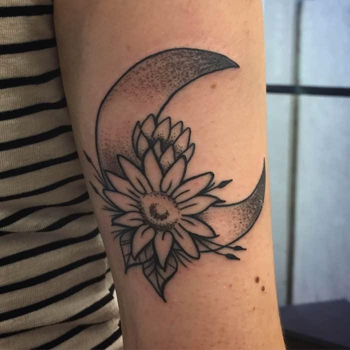 ein niedliches Tattoo mit einer Blume und dem Mond Tattoo Arten am Oberarm