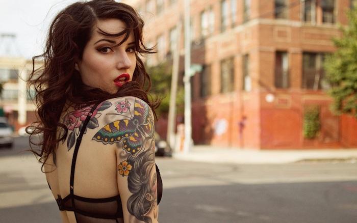schöne tattoos, frau mitmittellangen braunen lockigen haaren und tätoweirungen
