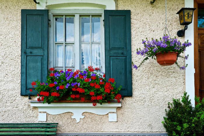 Blumen am Fenster, rote Geranie und blaue Petunien, romantischen Look zuhause schaffen