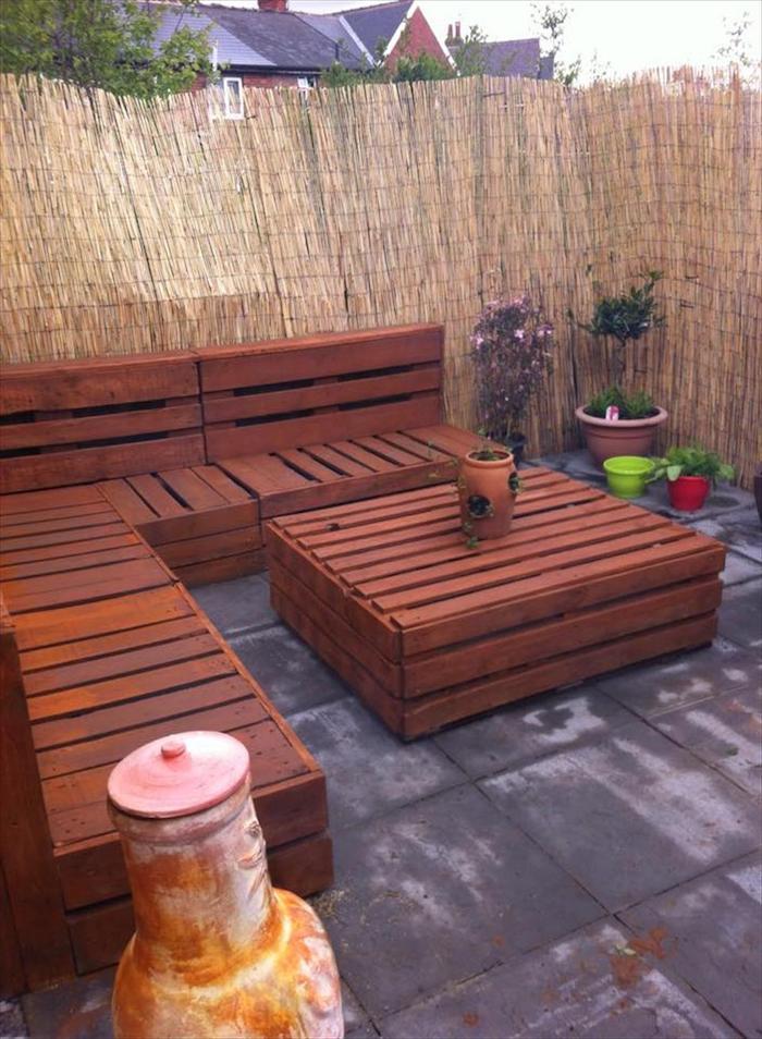 das ist eine idee für palettenmöbel für den auüenbereich - sofas und ein tisch aus den alten paletten und blumentöpfe