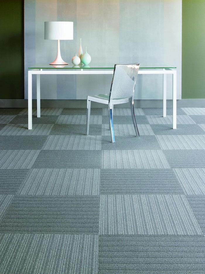 grauer Teppich in der Form von Fliesen, Design Fußboden ein Glas Tisch und eleganter Stuhl