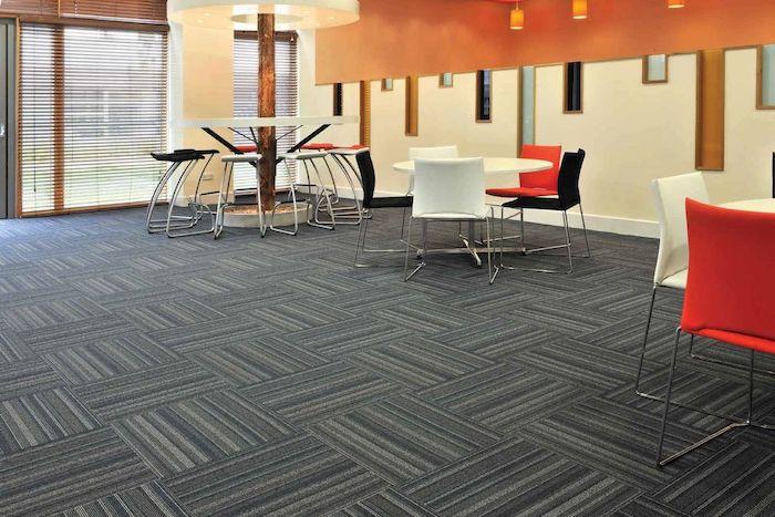 grauer Teppich auf Streifen wie Fliesen in einem Cafe bunte Stühlen und weiße Tische