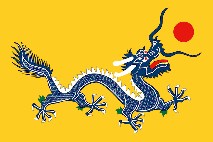eine blaue Drache mit weißen Stacheln und roter Zunge auf gelbem Hintergrund