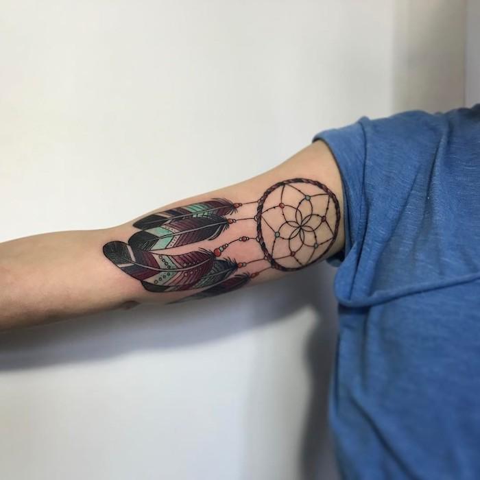 idee für einen tattoo auf der hand mit einem tattoo mit einem schwarzen traumfänger mit langen, schwarzen und grünen schönen federn