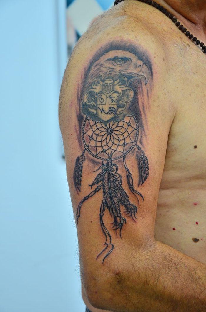 hier zeigen wir ihnen einen tattoo mit einem adler und einen schwarzen traumfänger mit langen federn auf dem schulter