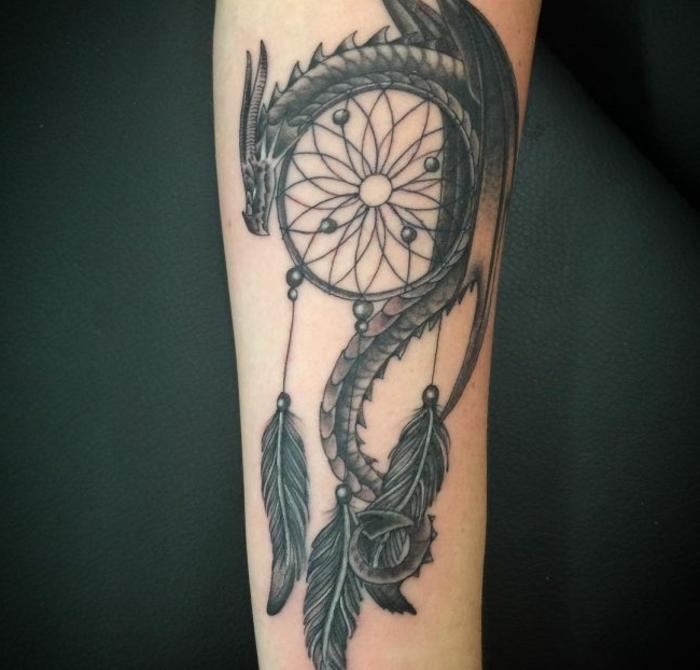 idee für eine tätowierung auf der hand - hier ist ein drachen und ein traumfänger mit langen schwarzen federn