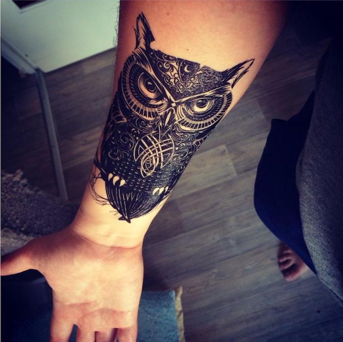 hier finden sie eine unserer ideen für einen schwarzen tattoo auf der hand - ein schwarzer uhu mit schwarzen federn