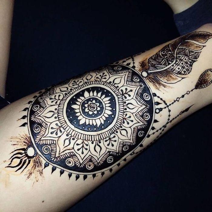 jetzt zeigen wir ihnen eine der besten ideen für tattoo dremcatcher mit mandala motiven und einem schwarzen feder auf der hand