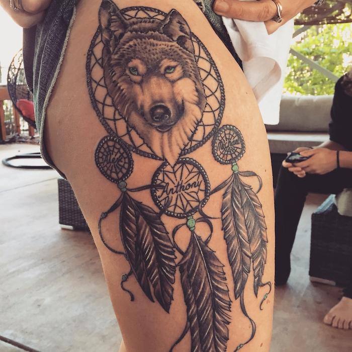 jetzt finden sie eine idee für einen tattoo mit einem schwarzen traumfänger mit langen federn und mit einem schwarzen wolf auf bein