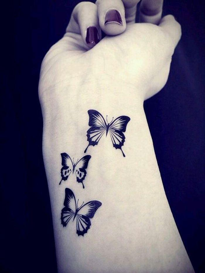 das ist eine der besten ideen zum thema schmetterling tattoo, die ihnen sehr gut gefallen kann - drei kleine, schwarze, fliegende schmetterlinge auf dem handgelenk einer hand einer jungen frau
