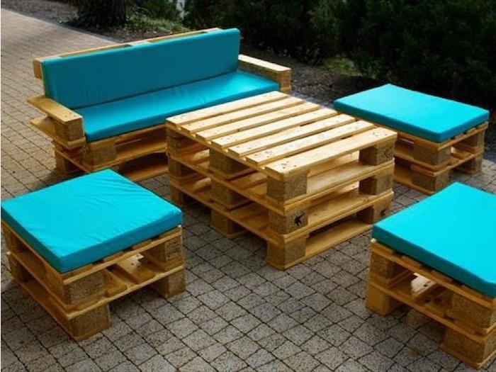 hier finden sie eine der besten ideen zum thema palettenmöbel terrasse - ein tisch und sofa mit schönen blauen kissen