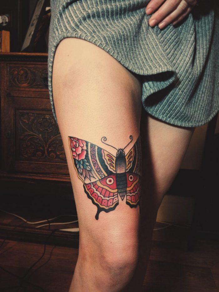 hier zeien wir ihnen eine unserer vielen ideen für einen schmetterling tattoo mit einem bunten großen schmetterling mit großen flügeln auf dem bein und mit einer roten rose - idee zum thema schmetterlinge tattoo für frauen