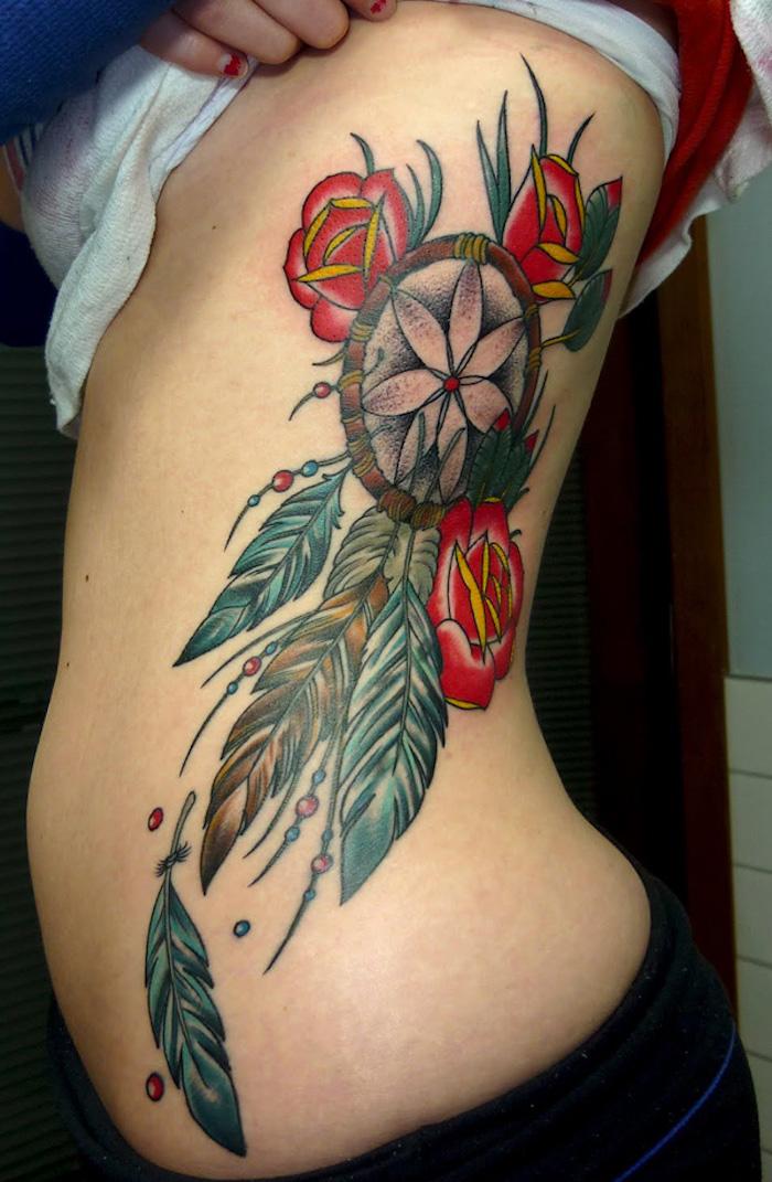 hier ist eine tolle tätowierung für eine frau - ein tattoo mit einem dreamcatcher und drei rosen und grünen tollen blättern