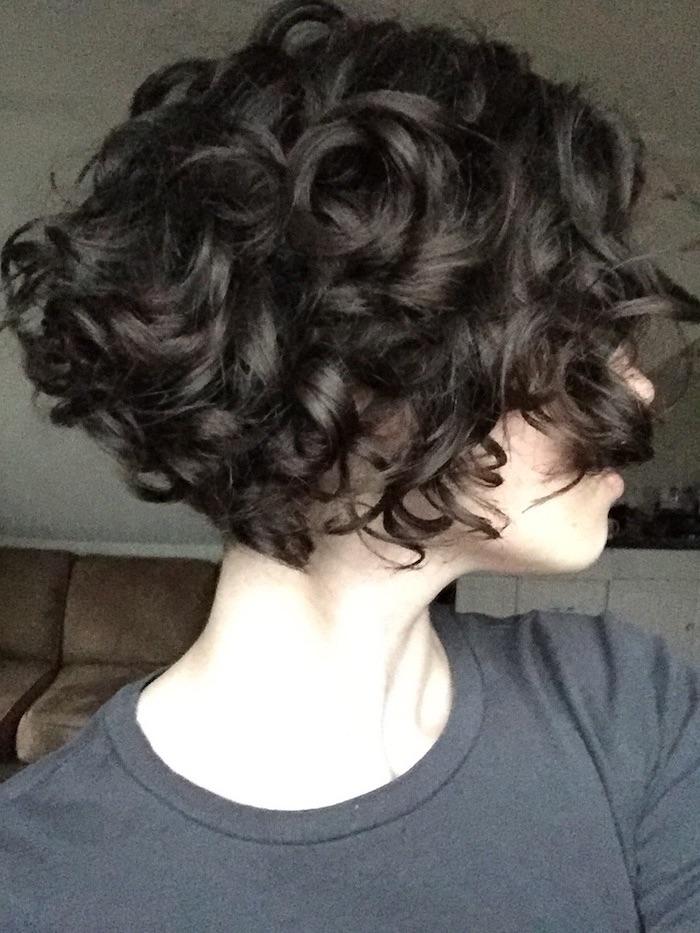 Kurzhaarfrisuren für lockiges Haar - schwarze Haare, weiße Haut und graue Bluse