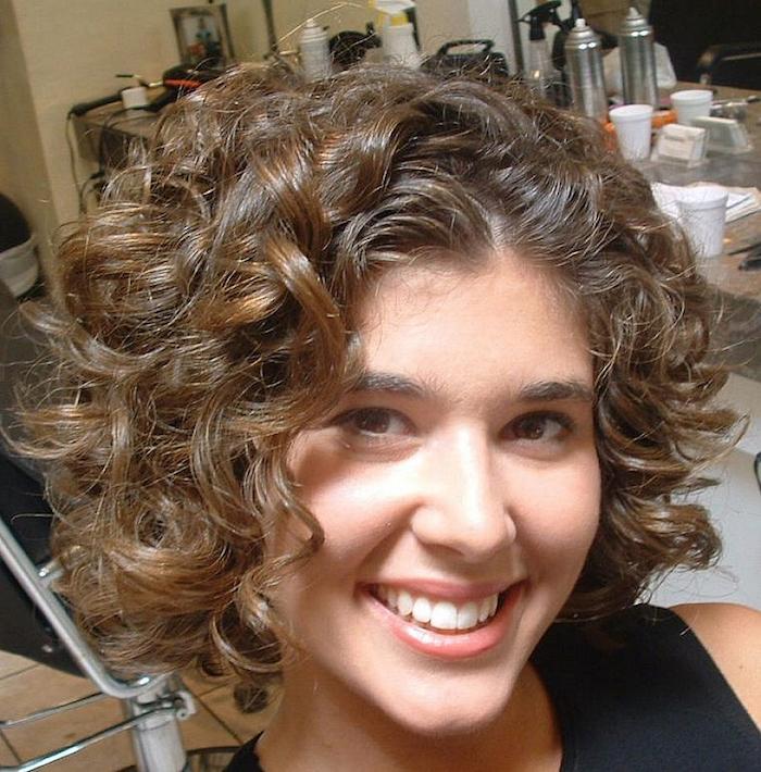 ein Mädchen mit einem schönen Lächeln das Kurzhaarfrisuren für lockiges Haar präsentiert