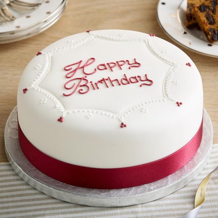 Torte zum Geburtstag, schön dekoriert mit weißem Guss und roten Punkten