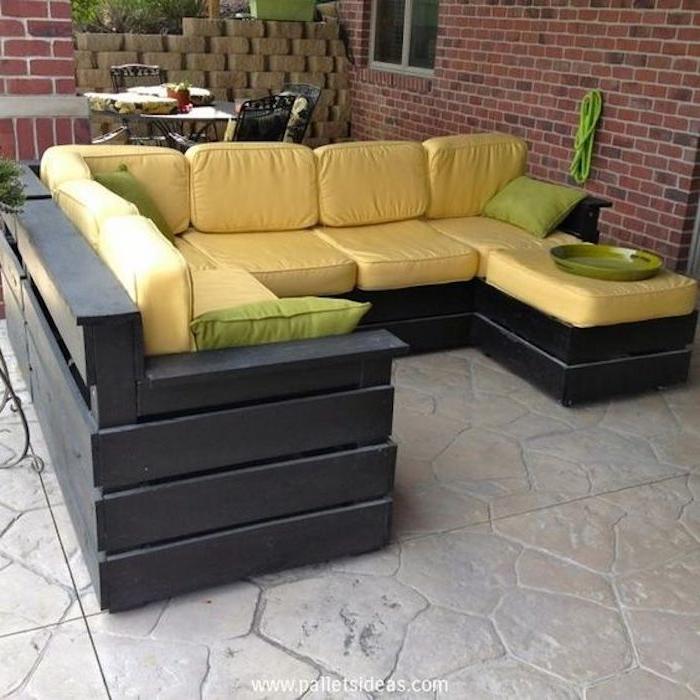 hier finden sie ein modernes schwarzes sofa mit gelben und grünen kissen für den außenbereich
