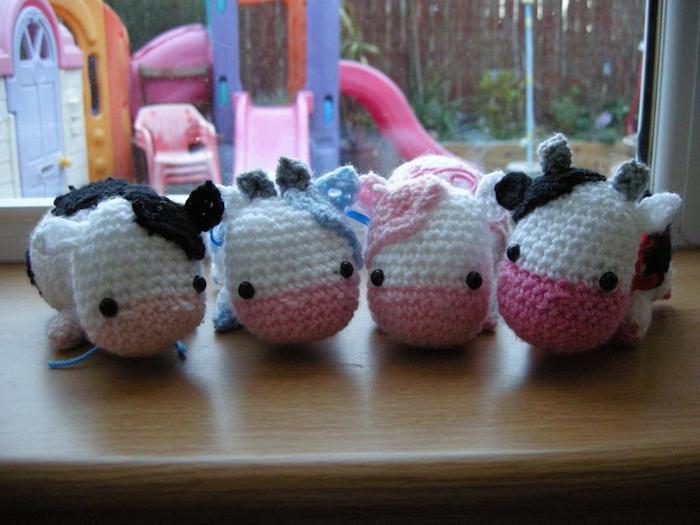 vier entzückende Kühe mit rosa Meule an dem Tisch geordnet Amigurumi für Anfänger