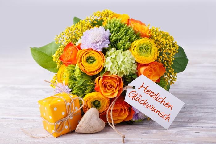 Blumenstrauß, kleines Geschenk und Geburtstagskarte, Geburtstagsglückwünsche