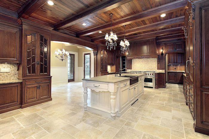 Bodenbelag Küche - eine Kochinsel in der Mitte, Fliesen in beiger Farbe, Möbel aus Holz