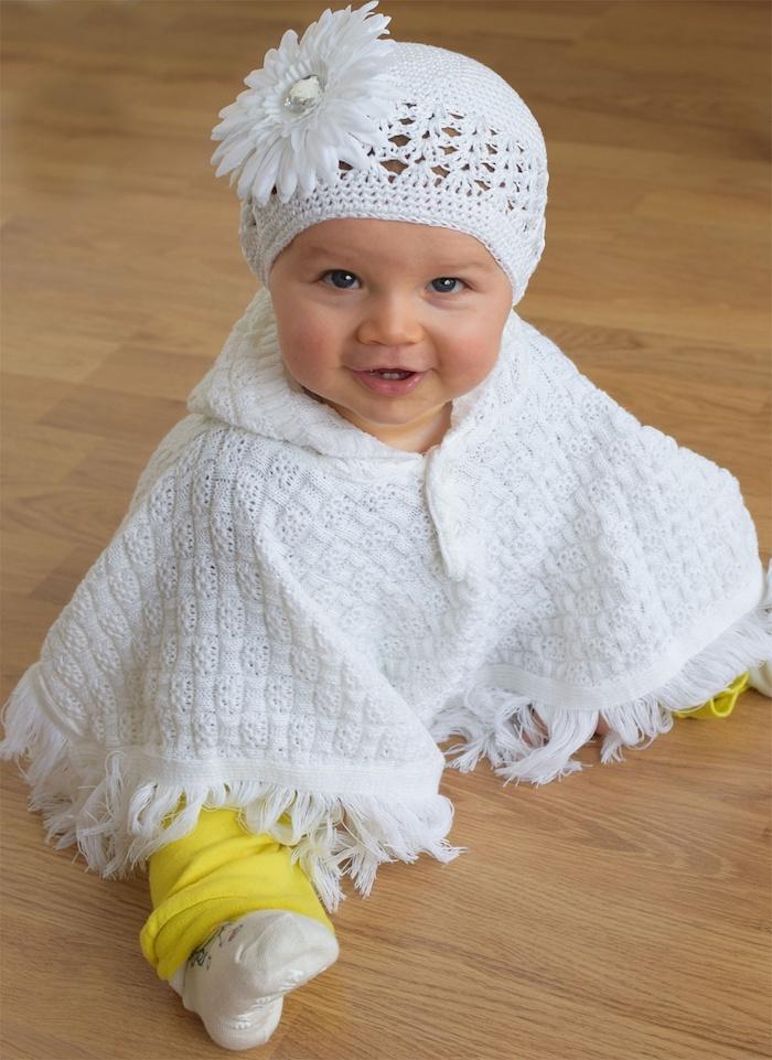 ein niedliches kleines Mädchen mit weißem Poncho, wie Sie für Baby Poncho stricken
