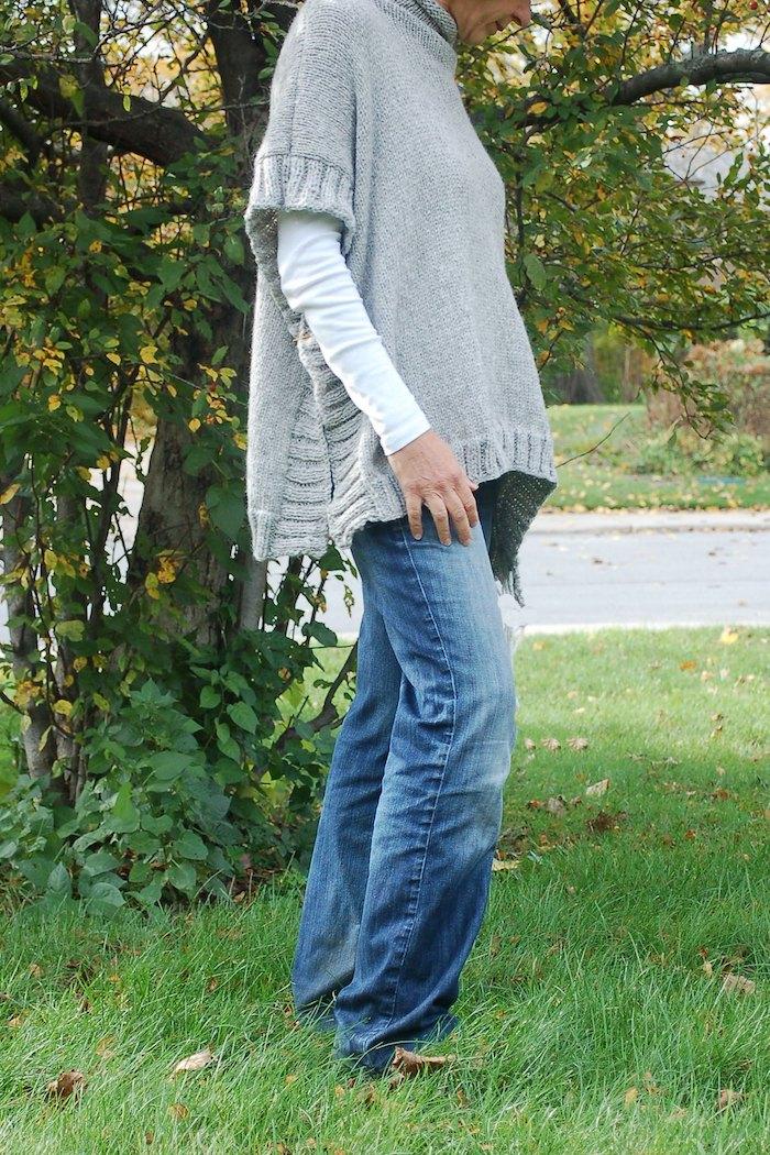 einen grauen Poncho stricken mit Muster an Rändern mit Jeans kombiniert
