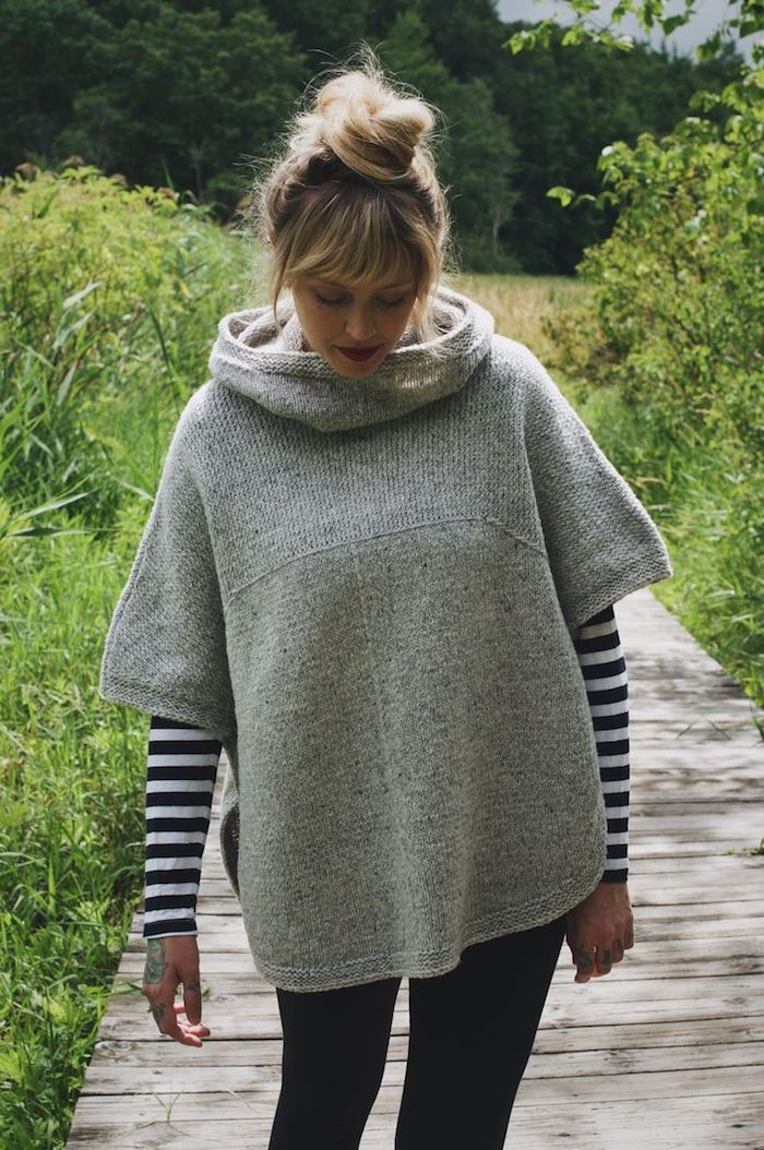 Poncho stricken in grauer Farbe, ein blondes Model in dem Garten auf dem Pfad