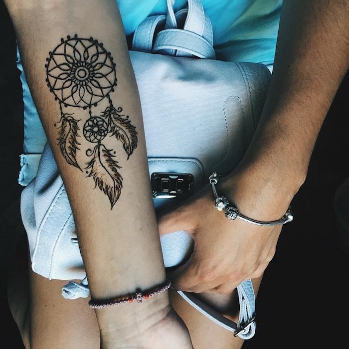 hier finden sie eine hand mit einem traumfänger tattoo mit schwarzen kleinen schönen federn und eine hand mit einem armband