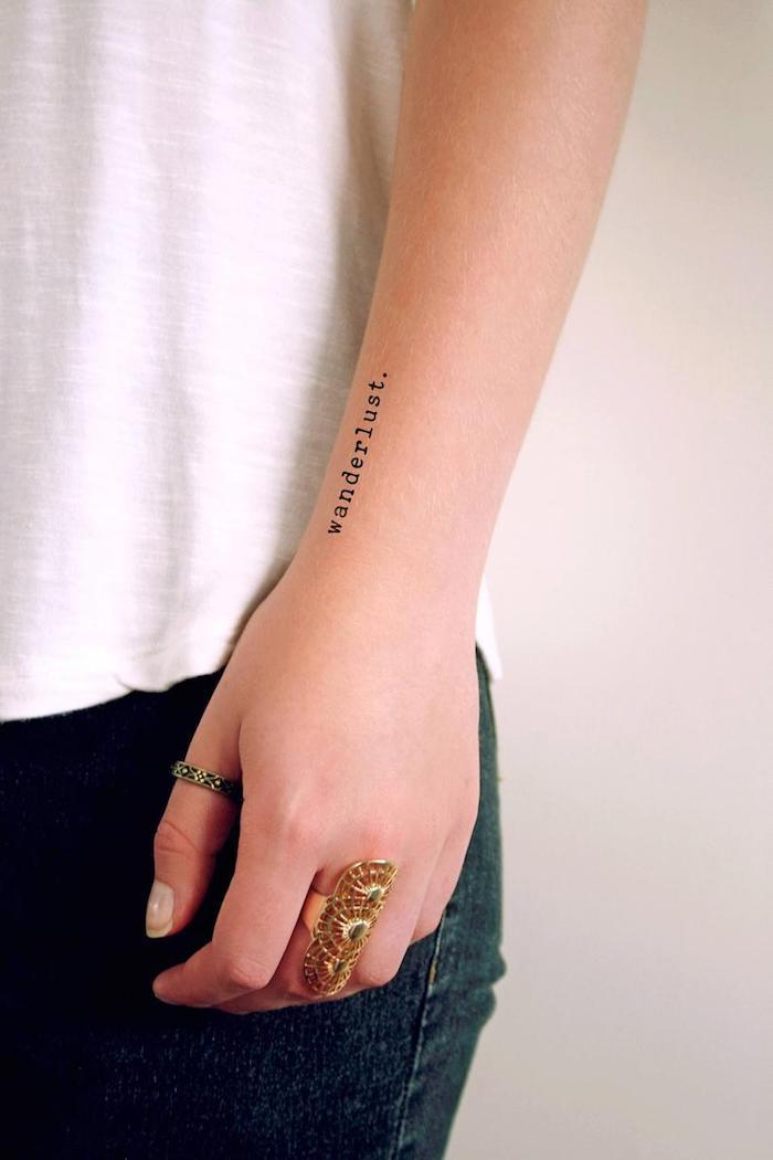 Kleines Tattoo am Unterarm im Schreibmaschinenstil, Wanderlust Tattoo, goldene Ringe, weißes Top und Jeans