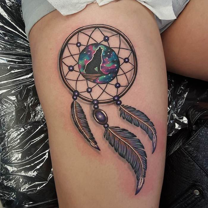 tattoo mit einem schönen schwarzen kleinen heulenden wolf und einem großen traumfänger und drei schwarzen federn