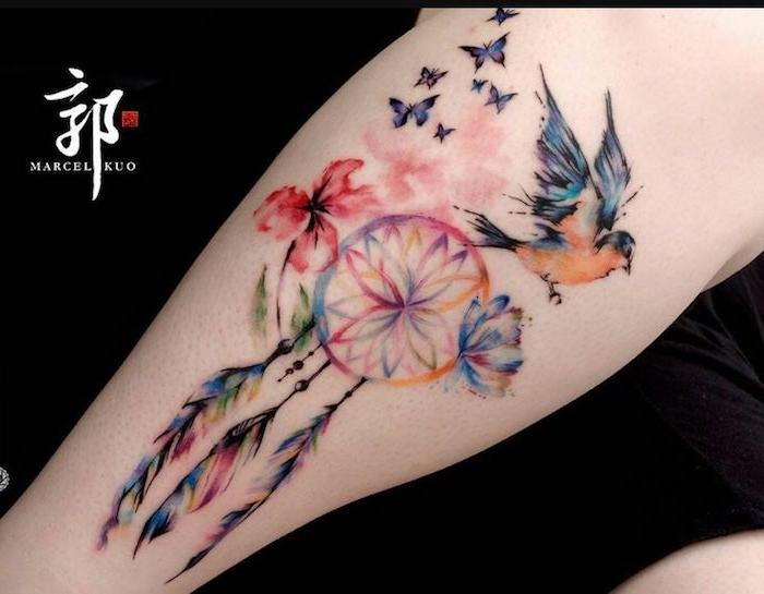 jetzt finden sie eine idee für einen märchenhaften tollen bunten watercolor tattoo mit lila schmetterlingen, traumfänger, bunten federn, einem kleinen vogel und zwei blumen