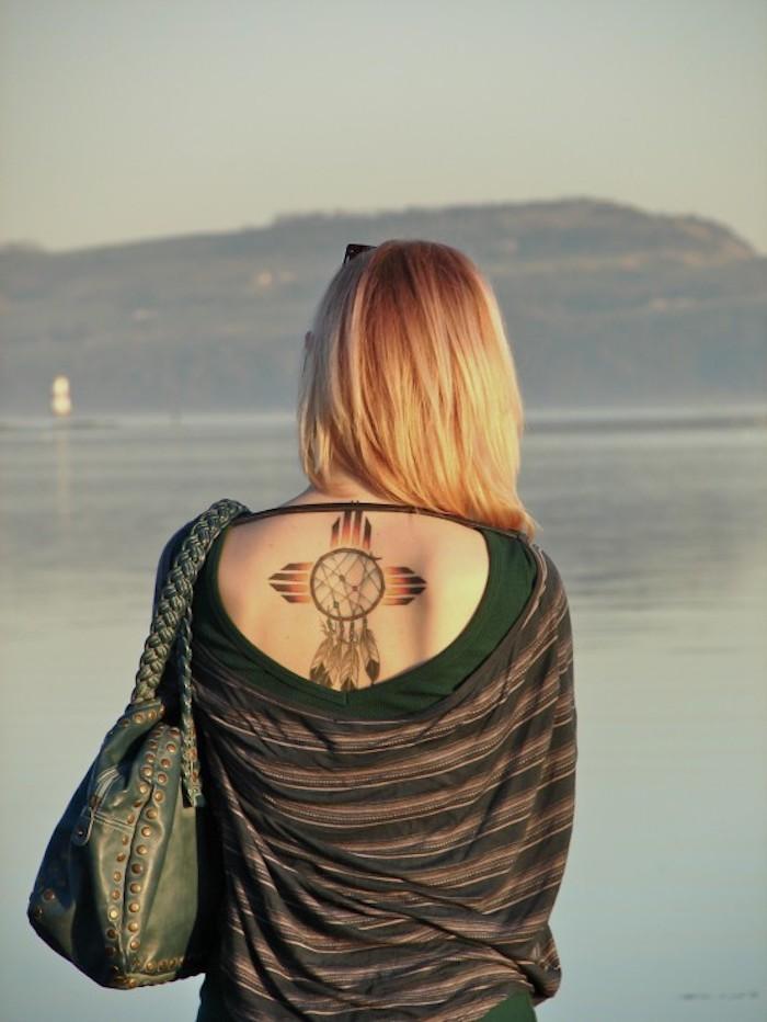 eine idee für einen winzigen tattoo mit traumfänger und kreuz auf dem rücken einer jungen frau