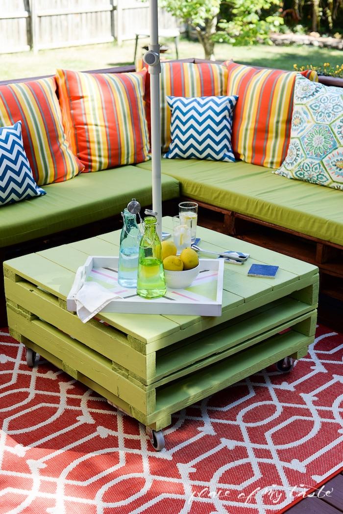 jetzt zeigen wir ihnen eine unserer ideen für einen tisch und sofa mit grünen und bunten kissem - möbel aus europaletten für den außenbereich - tisch, flaschen, gläser