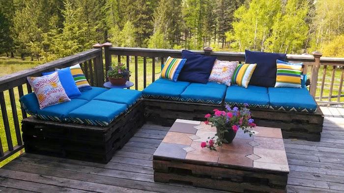 garten, bäume, terrasse, palettenmöbel für den außenbereich - hier sind moderne sofas mit kleinen blauen kissen und ein tisch, die aus alten europaletten gebaut wurden - ein tisch mit einer kleinen vase mit lila und oinken blumen
