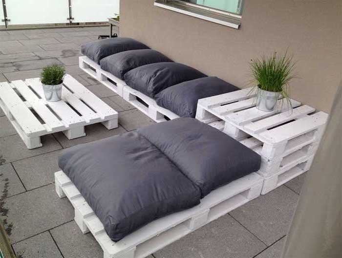 jetzt zeigen wir ihnen eine idee zum thema palettenmöbel sofa - hier sind weiße hocker und tisch aus alten paletten und zwei vasen mit grünen pflanzen