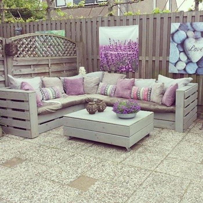 diese idee zum thema palettenmöbel terrasse könnte ihnen sehr gut gefallen -zwe weiße sofas mit lila kissen und ein tisch aus alten weißen europaletten mit blumentöpfen mit schönen lila blumen