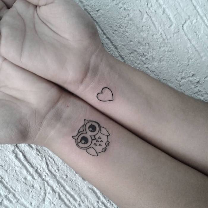 hier sind zwei kleine mini schwarze tattoos mit einer eule und einem kleinen herzen auf handgelenk
