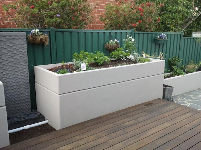 weißes Hochbeet selber bauen an einem Zaun in grüner Farbe Hochbeet nach Gießen