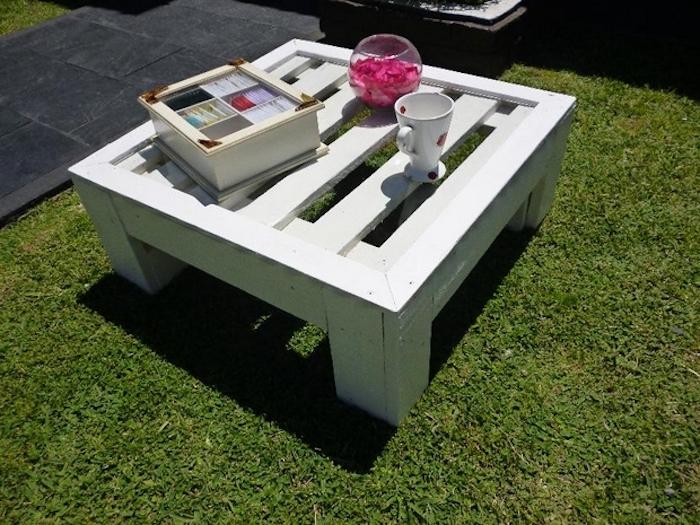 jetzt zeigen wir ihnen palettenmöbel für den außenbereich - hier ist ein kleiner tisch aus weißen europaletten mit einer tasse und einer vase
