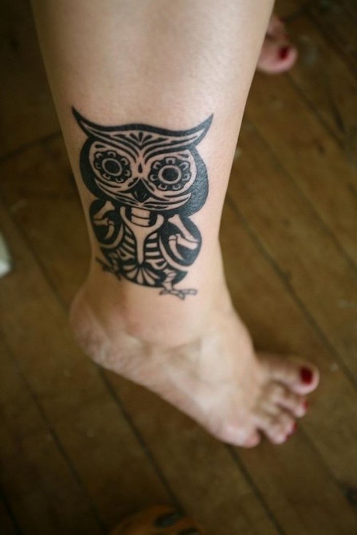 hier ist ein bein mit einem schwarzen tattoo mit einer schwarzen eule - idee für eine schwarze tätowierung owl