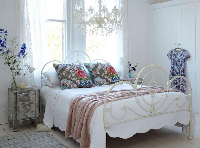 shabby möbel im schlafzimmer, großes bett im retro stil, bunte dekokissen mit blumen