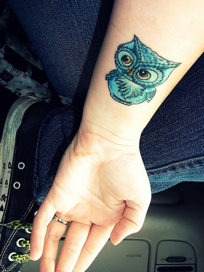 eine hand mit einem owl tattoo auf handgelenk - blaue kleine eule mit gelben augen