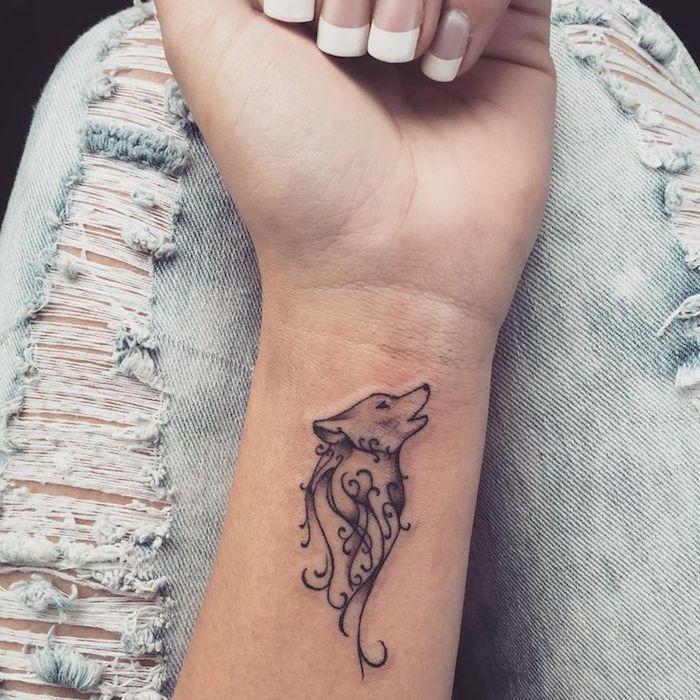 beliebteste tattoos, kleine tätowierung mit wolf-motiv am handgelenk