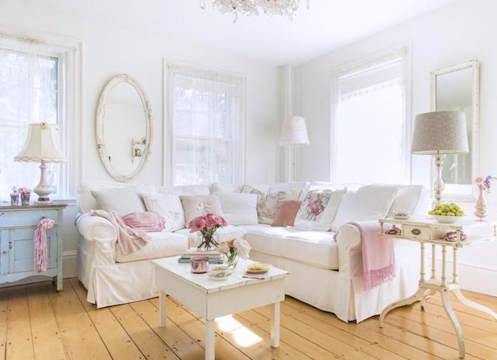 shabby deko, weißer ecksofa dekoriert mit dekokissen mit blumen, ovaler spiegel, mit weißem rahmen