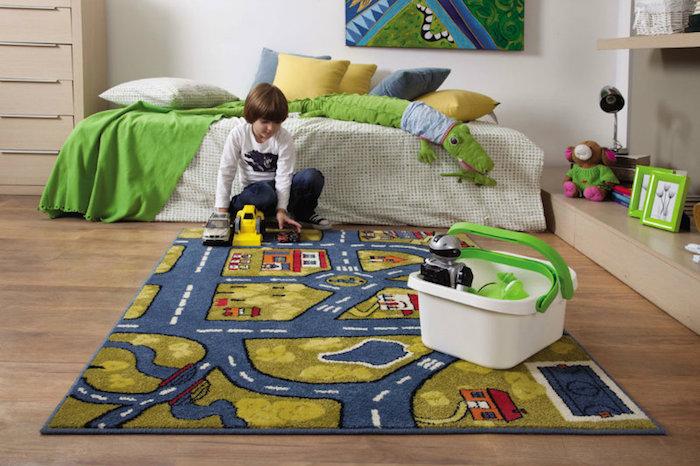 ein Junge spielt im Kinderzimmer, Polizeiauto, Bagger, Holzkommode, gelbe Bettkissen