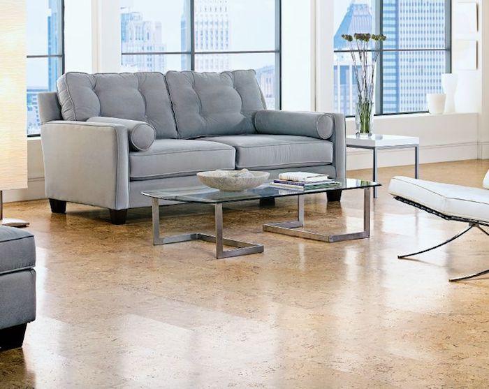 Korklaminat, großes helles Wohnzimmer mit grauen Möbeln und großen Fenstern