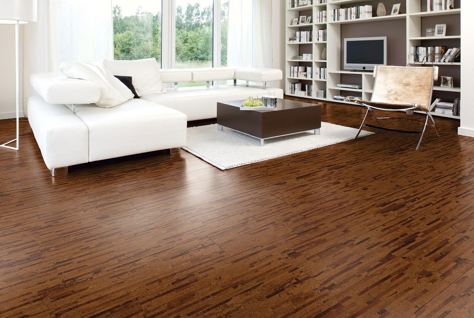weißes Sofa kleiner brauner Tisch Regalsystem mit Büchern Kork Fußbodenbelag