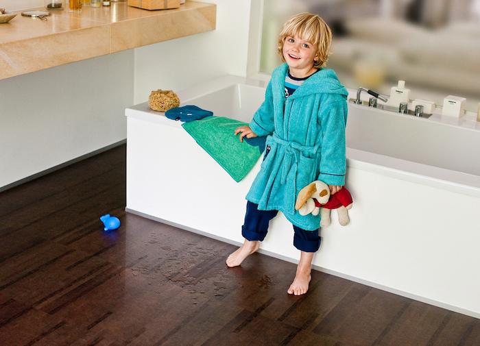 ein glückliches Kinde mit blauem Morgenmantel aus Plüsch, Marmortischplatte
