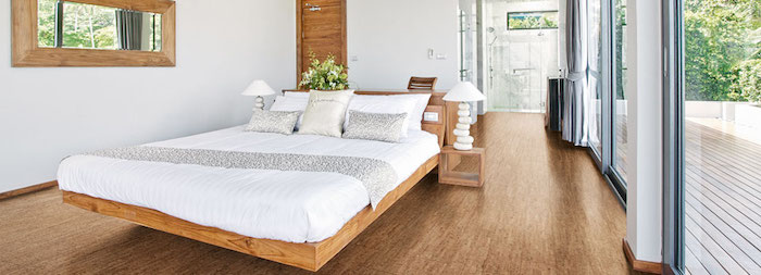 warmes Schlafzimmer mit weißen Wänden und Übergang zum Badezimmer